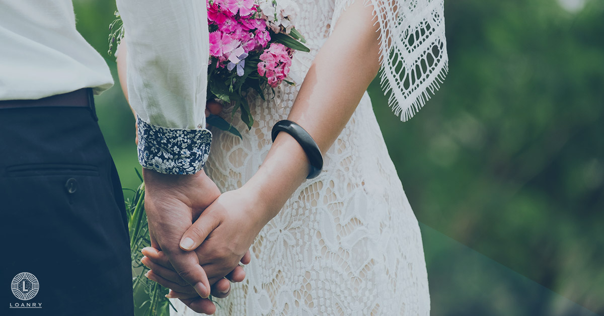 A couple holding hands on their wedding day