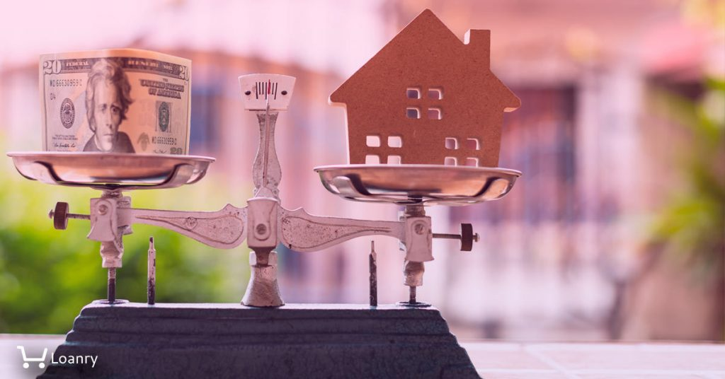 House model and money on weight scale with out of focus home.