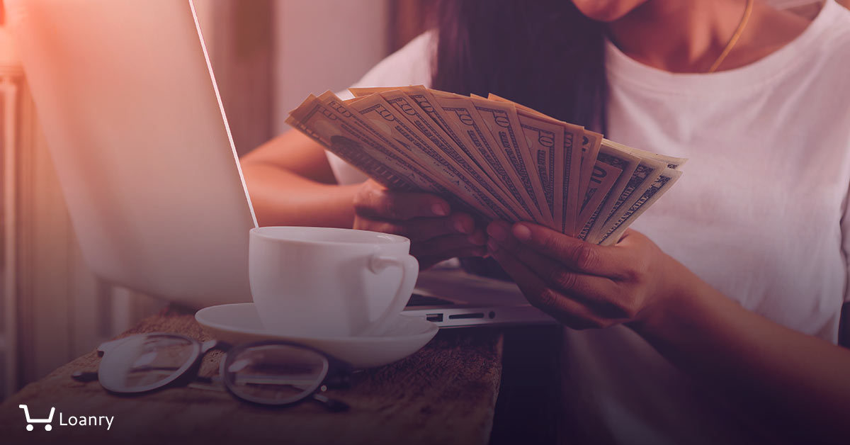 woman holding stack of dollars while using her laptop