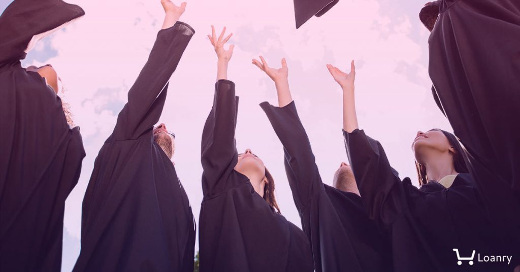 Low angle view of happy group of six young cheerful graduates in black gowns, throwing up their head wear in the air and celebrating.