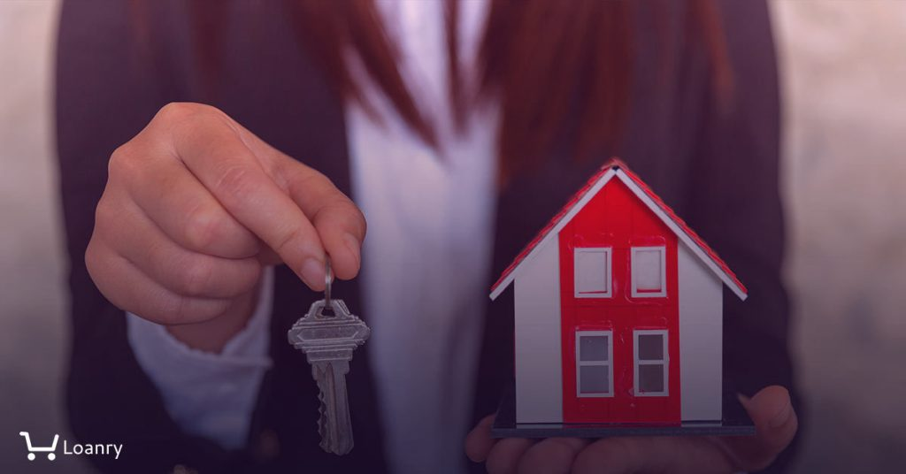 A real estate agent with a key. Red roof house.