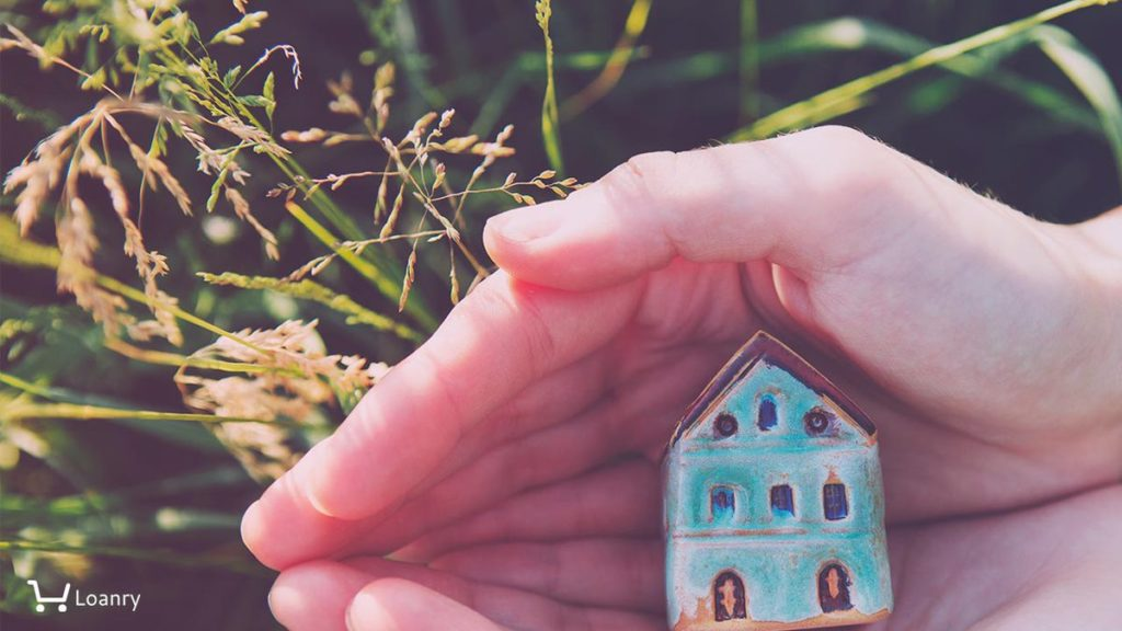 Female hands holding small house, natural background