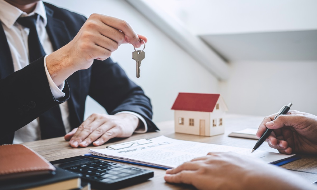 Estate agent giving house keys to client after signing agreement contract real estate with approved mortgage application form.