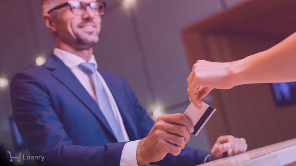 Businessman in suit and glasses giving credit card to woman
