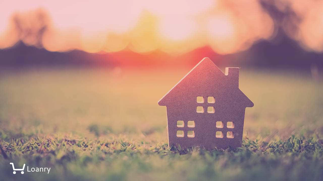 Small model home on green grass with sunlight abstract background