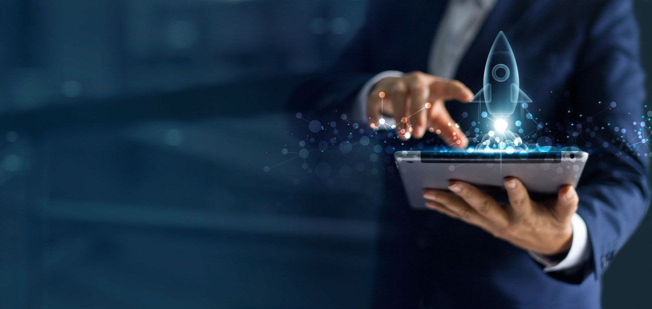 Businessman holding tablet and icon transparent rocket is launching and soar flying out from screen.